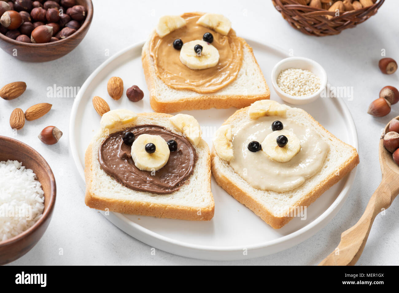 Vegan nut butter toasts with animal faces. Healthy breakfast for kids. Selective focus. Concept of vegan, healthy lifestyle, peanut butter banana, foo - Stock Image