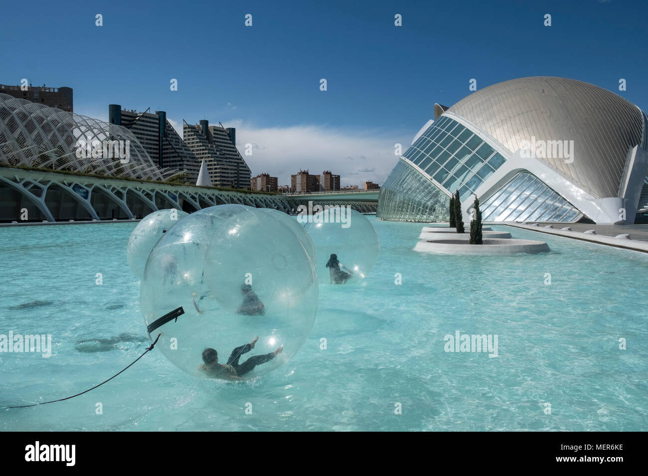Young children having fun inside a water walking ball in L'Hemisferic building pool area, City of Arts and Sciences, Valencia, Spain. - Stock Image
