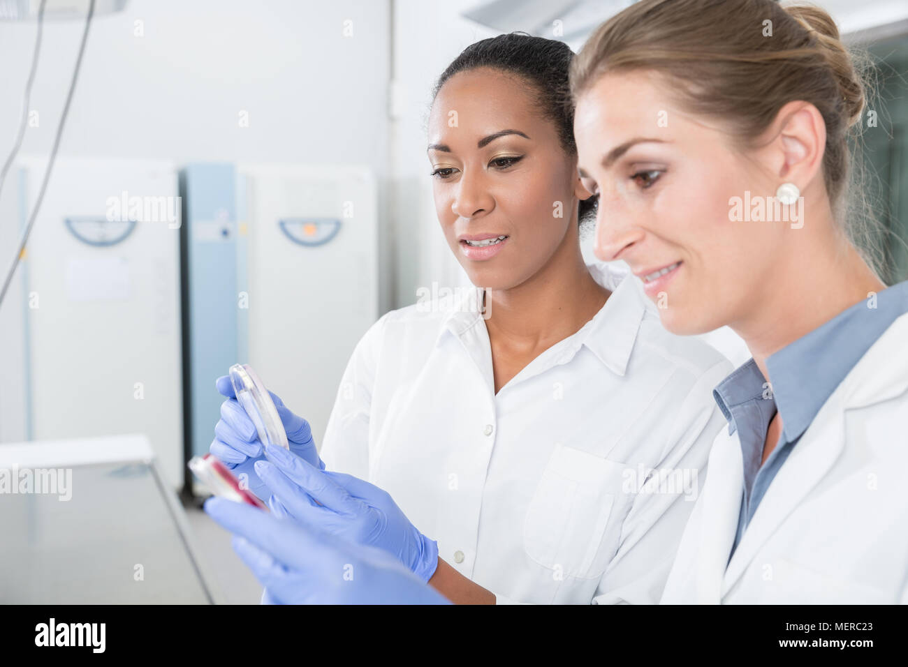 Scientists in research lab with analyzing instrument talking about results - Stock Image