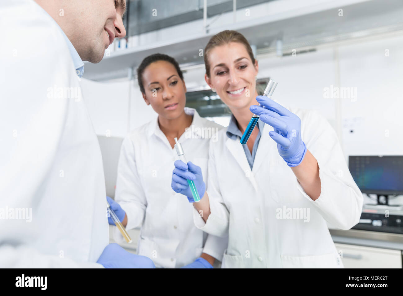 Researchers doing experiment in science lab  - Stock Image