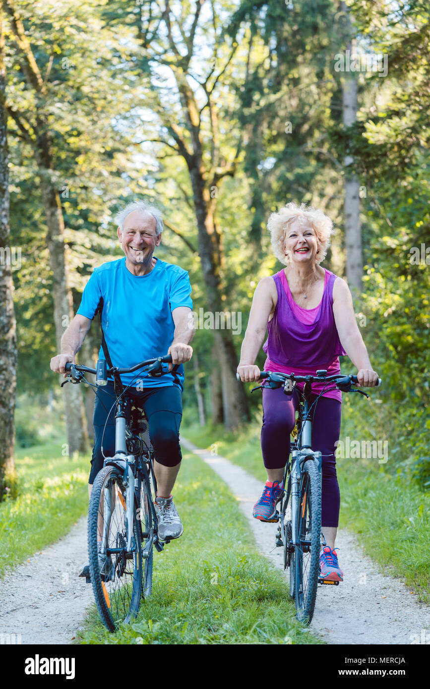 Happy and active senior couple riding bicycles outdoors - Stock Image
