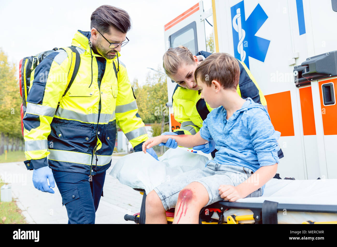 Emergency doctors caring for accident victim boy Stock Photo