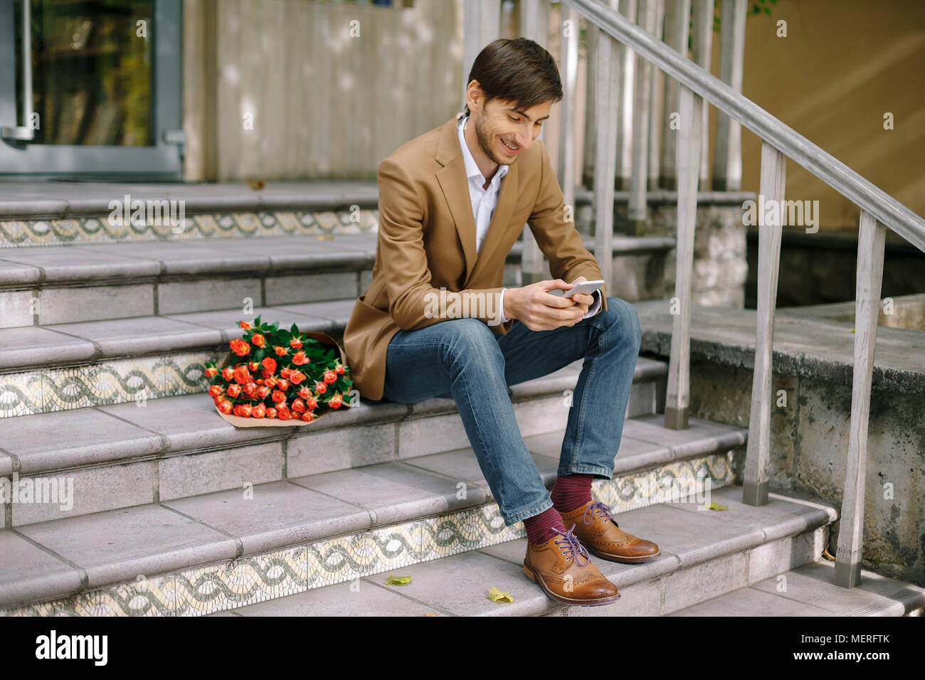Smiling man texting while looking at the phone - Stock Image