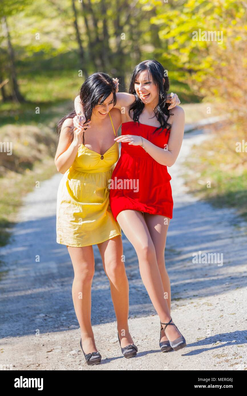 Girls in nature legs and heels walking drunk careless smile smiling loudly laughing laugh helping hand hands - Stock Image