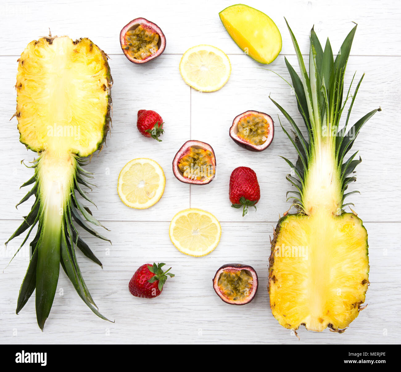 Looking down from above onto the fresh fruit such as passion fruit,mango, strawberry and pineapple which are the ingredients for a tropical smoothie. - Stock Image