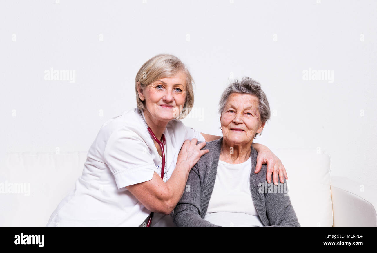 Studio portrait of a senior nurse and an elderly woman. - Stock Image