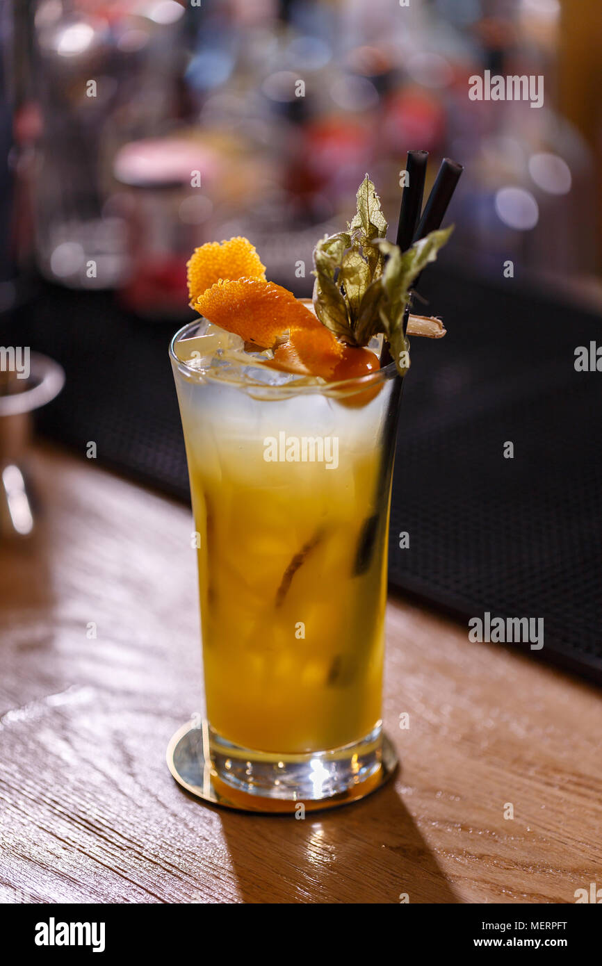 Fresh cocktail with orange and ginger served on the bar counter - Stock Image