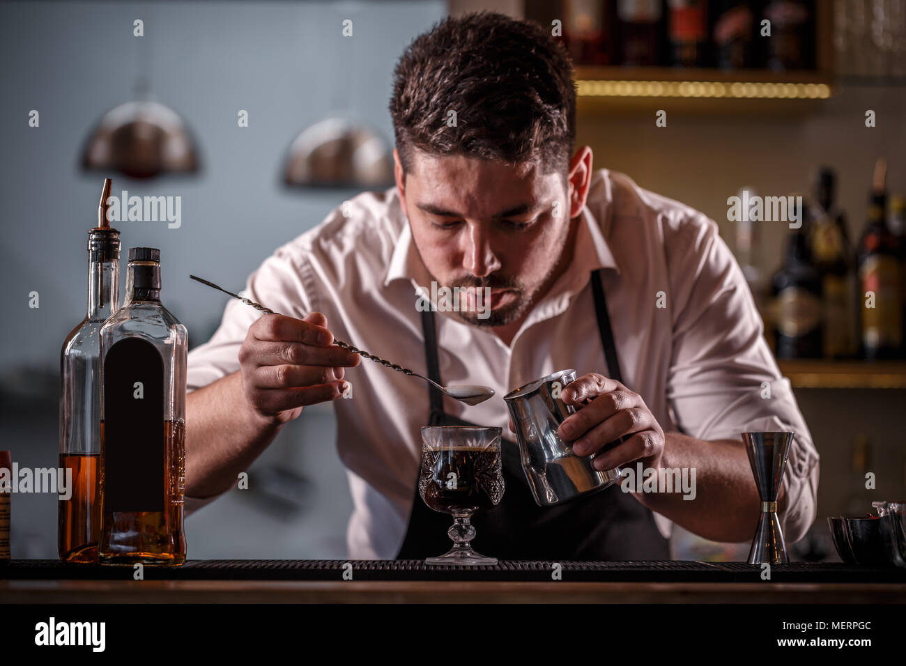 Bartender decorating coffee cocktail with milk foam - Stock Image