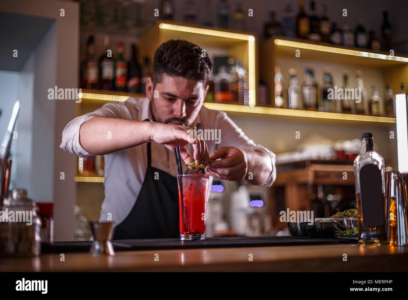 Bartender decorating non-alcoholic pomegranate cocktail with lime slices - Stock Image