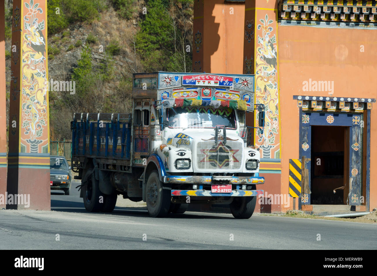Decorate truck passing through gateway at entrance to city, Thimphu, Bhutan - Stock Image