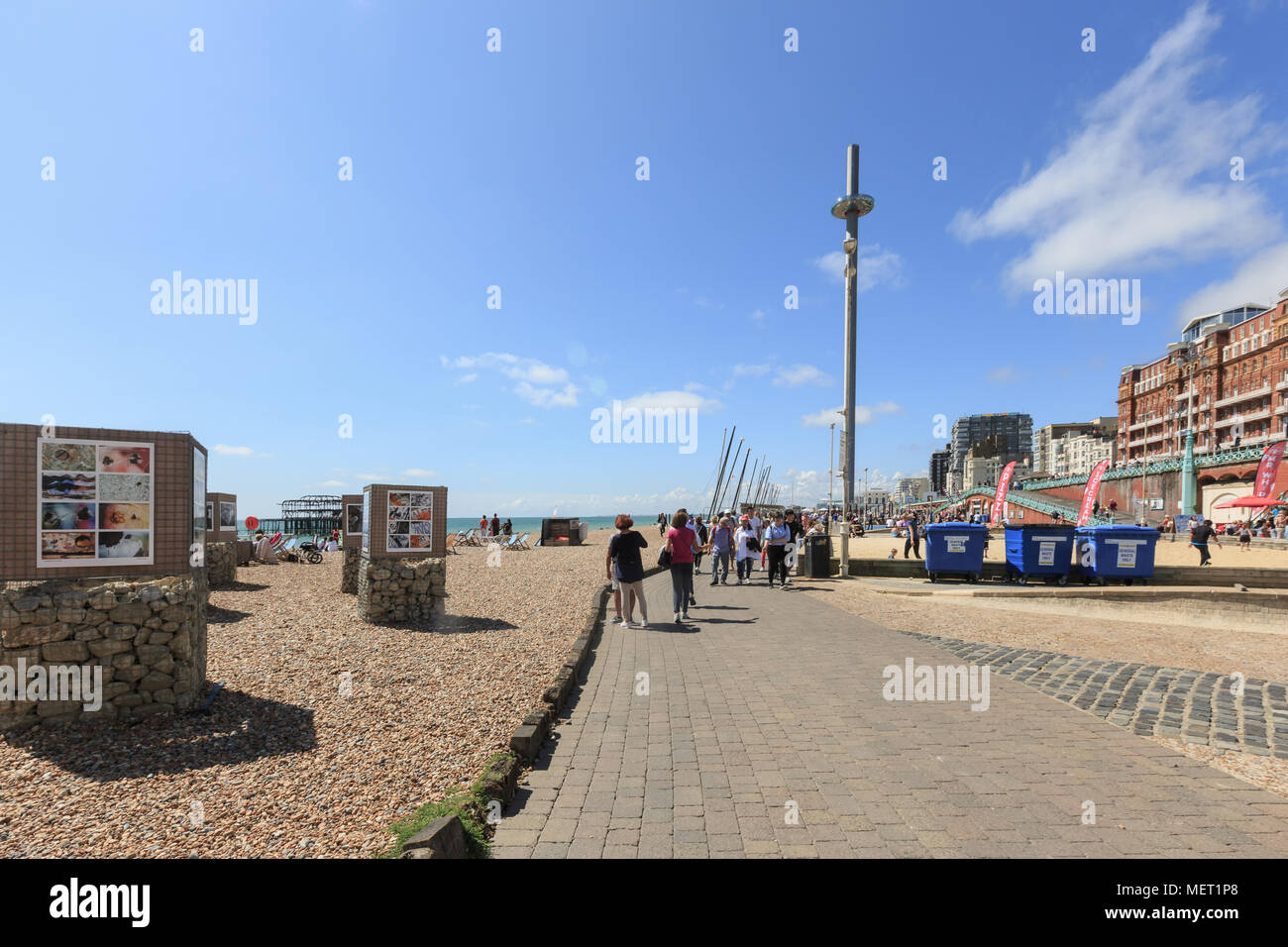 People admire walking on Brighton costline, view of English channel, tower i360 - Stock Image
