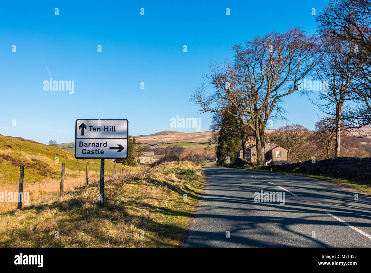 Looking up the road with a Tan Hill and Barnard Castle sign in the Arkengarthdale valley, Swaledale, Yorkshire Dales, UK - Stock Image