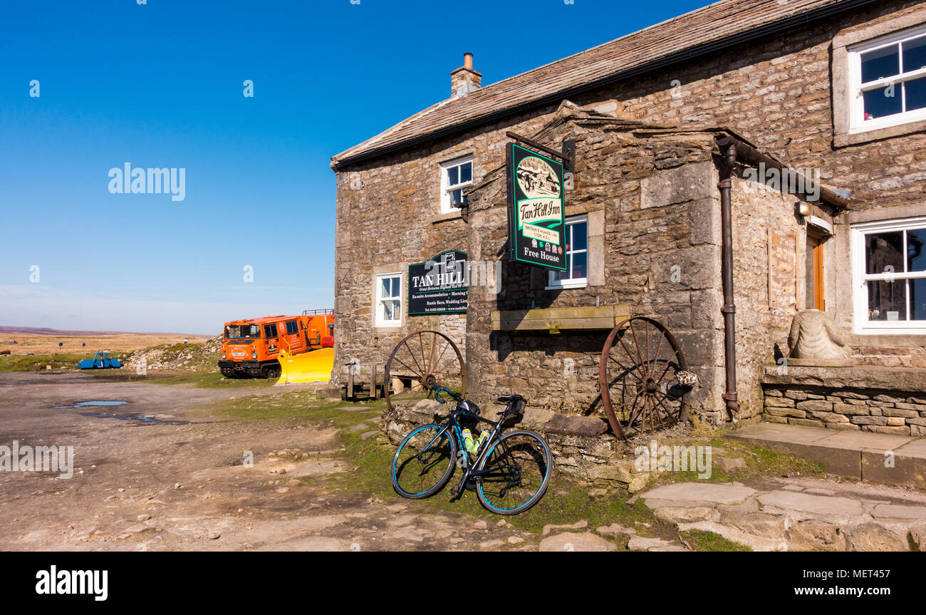 Tan Hill pub with a road bike and a snowplough outside, UK - Stock Image