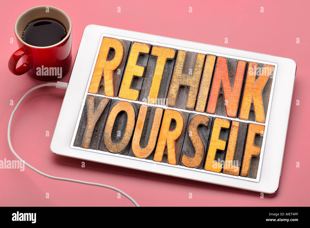 rethink yourself  word abstract in vintage letterpress wood type blocks on a digital tbalet with a cup of coffee - Stock Image