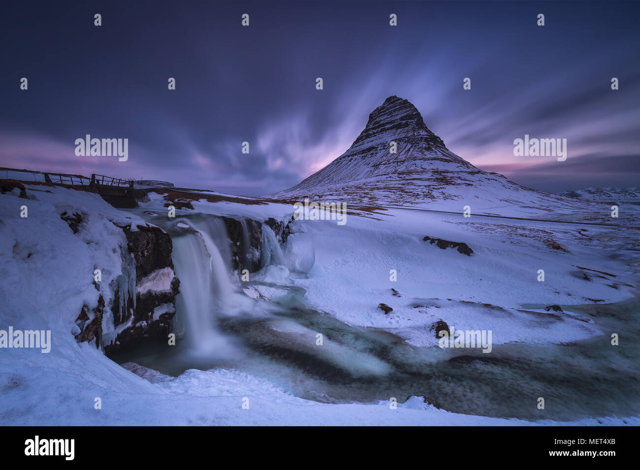 Kirkjufell and Kirkjufellfoss snowed in a cold winter - Stock Image
