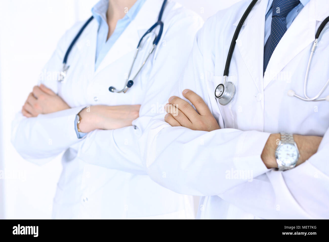 Team of unknown doctors standing straight with arms crossed in hospital. Physicians ready to help. Healthcare, insurance and medicine concept - Stock Image