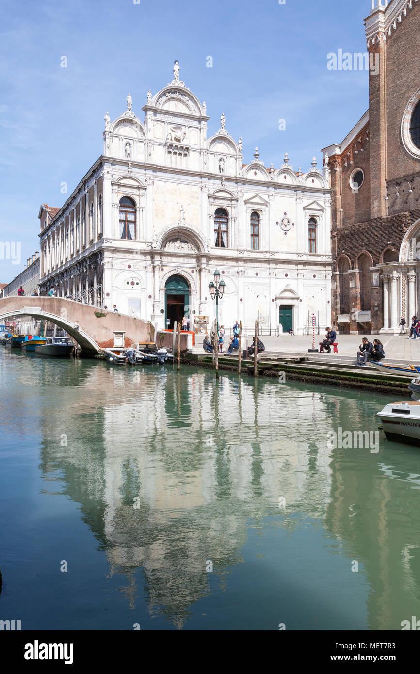 Scuola Grande di San Marco, Campo dei Santi Giovanni e Paolo, Castello, Venice, Veneto, Italy with reflection in the canal. It is now a civic hospital - Stock Image
