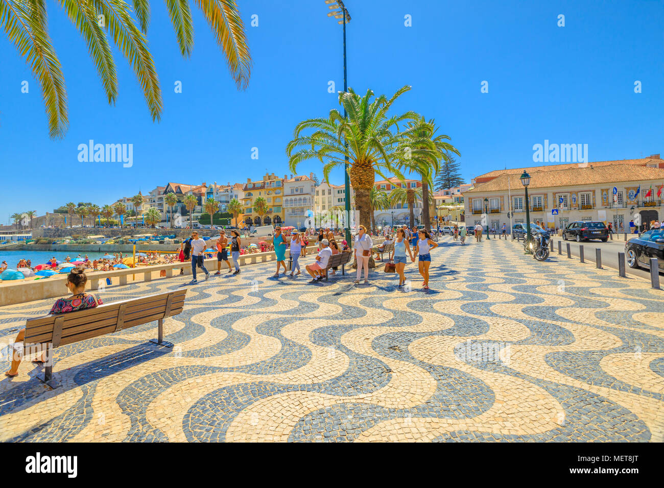 Cascais, Portugal - August 6, 2017: promenade along Ribeira beach on Passeio Dom Luis I street. Cascais is popular summer vacation spot in Lisbon Coast, Portugal. People enjoying summer holidays. - Stock Image