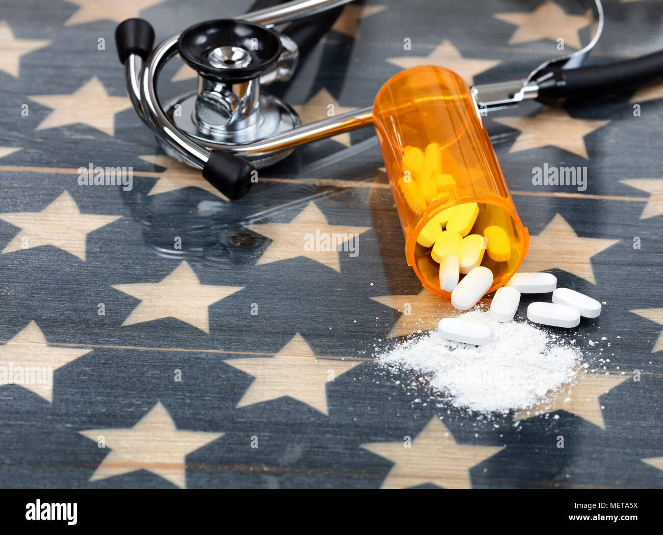 Close up front view of prescription bottle with generic opioid pain killer tablets. Rustic USA flag and medical stethoscope in background for drug add - Stock Image