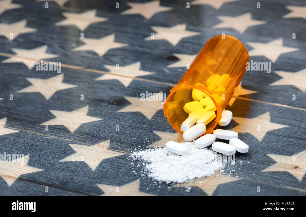 Front view of prescription bottle filled with generic opioid pain killer tablets on rustic USA flag in background for drug addiction concept in Americ - Stock Image