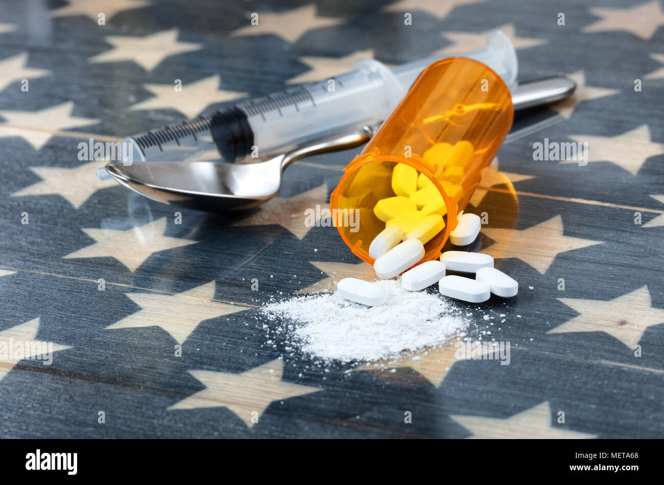 Front view of opioid pain killer tablets with spoon and syringe on rustic USA flag in background for drug addiction concept in America - Stock Image