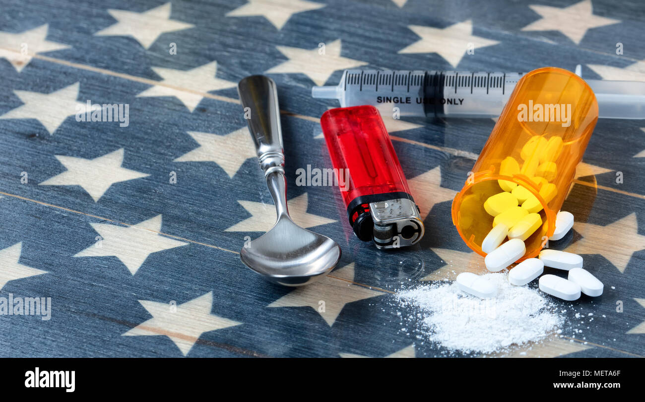 Front view of opioid pain killer tablets with spoon, lighter and syringe on rustic USA flag in background for drug addiction concept in America - Stock Image