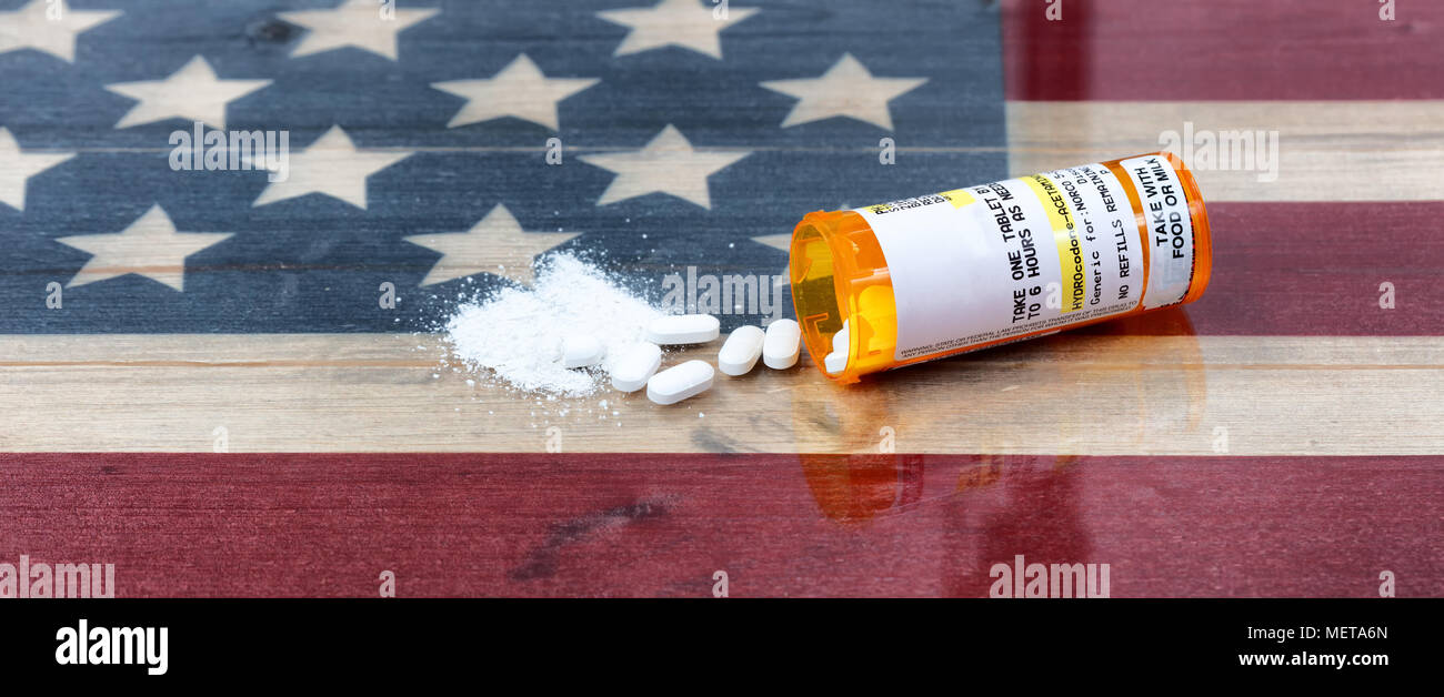 Bottle of prescription for Hydrocodone or generic opioid with crushed or whole pain killer tablets. Rustic USA flag in background for drug addiction c - Stock Image