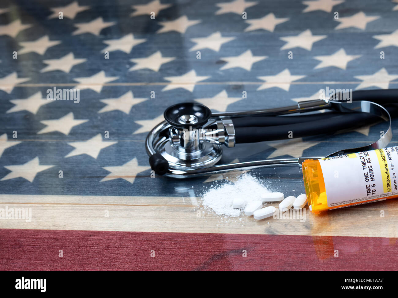 prescription for Hydrocodone or generic opioid with crushed or whole pain killer tablets. Rustic USA flag and medical stethoscope in background for dr - Stock Image