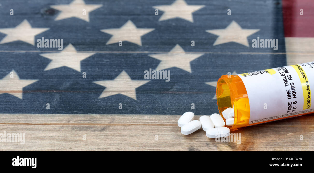 Prescription bottle of Hydrocodone or generic opioid pain killer tablets with rustic USA flag in background for drug addiction concept in America - Stock Image