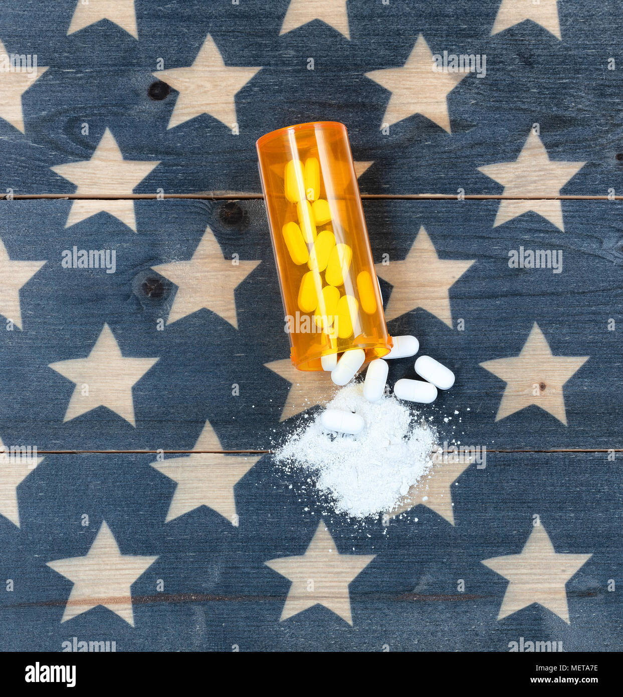 Overhead view of prescription bottle filled with generic opioid pain killer tablets on rustic USA flag in background for drug addiction concept in Ame - Stock Image