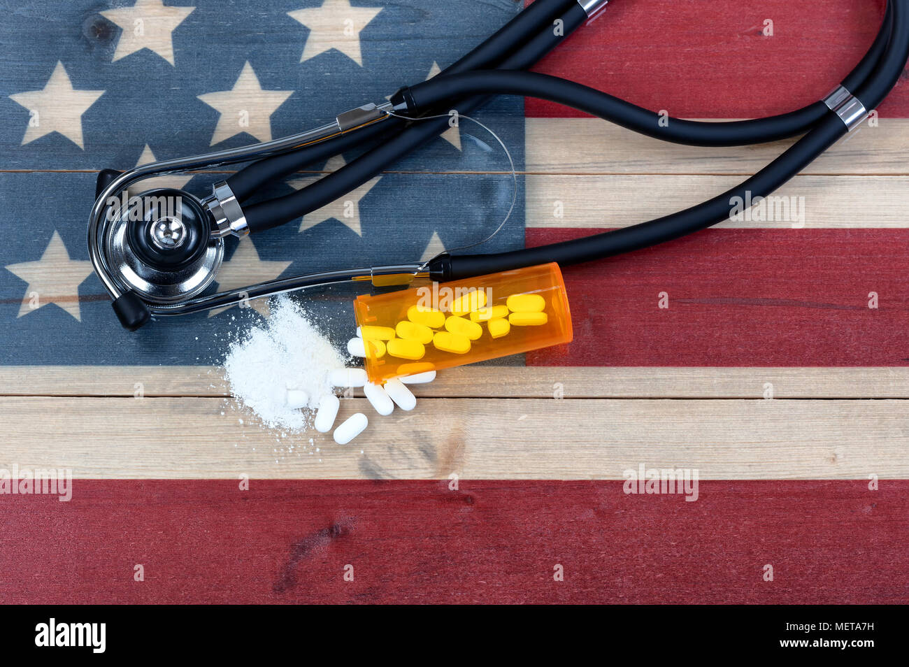 Overhead view of prescription for generic opioid with crushed or whole pain killer tablets. Rustic USA flag and medical stethoscope in background for  - Stock Image