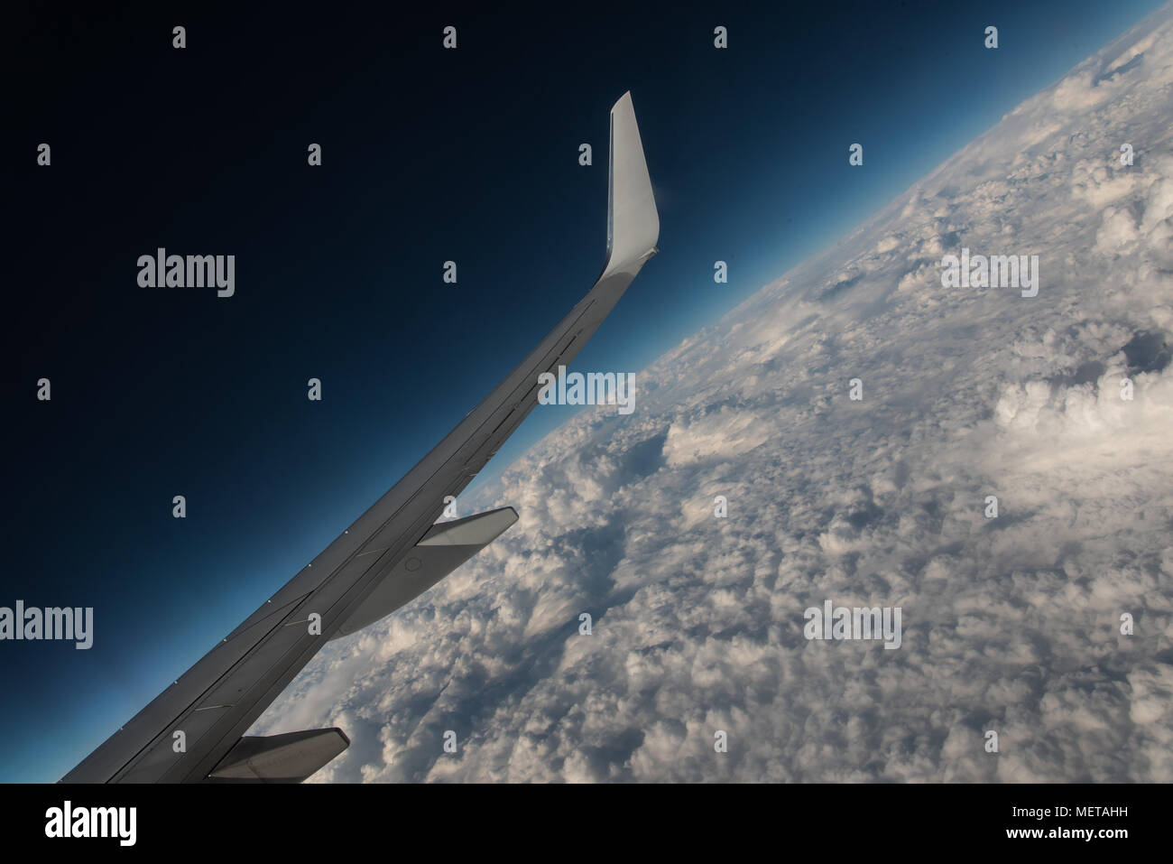 Jetliner Wing Over Clouds - Stock Image