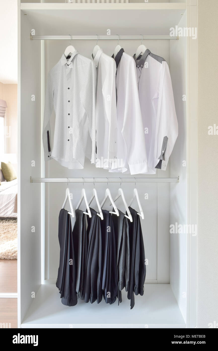 f3efe79be3 row of white shirts and black pants hanging in wooden wardrobe Stock ...