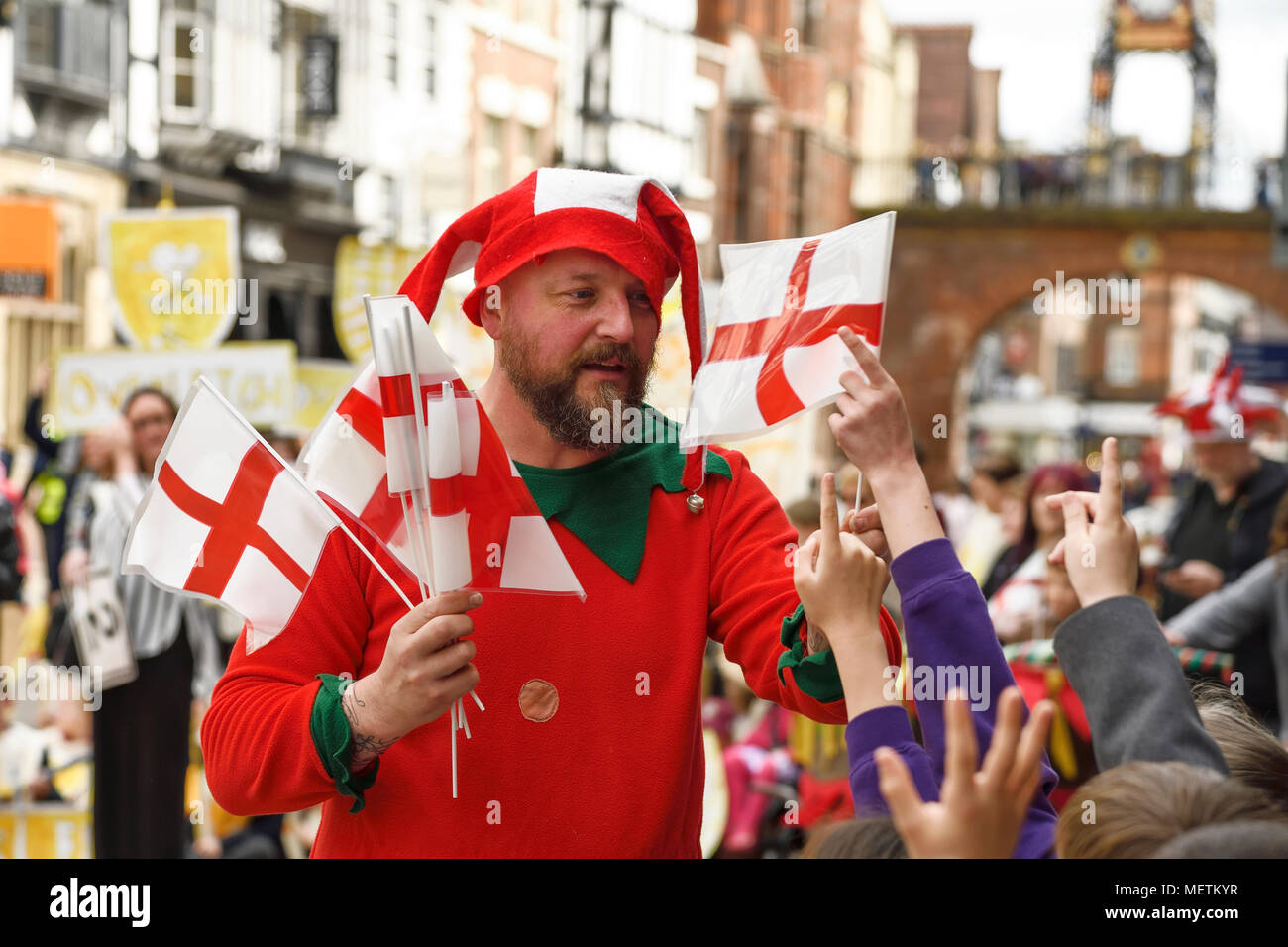 Chester, UK. 23rd April 2018. A jester hands out flags in the St George's Day parade through Chester city centre. The parade includes street performance, theatre and music with local school children performing many supporting roles. Credit: Andrew Paterson/Alamy Live News - Stock Image