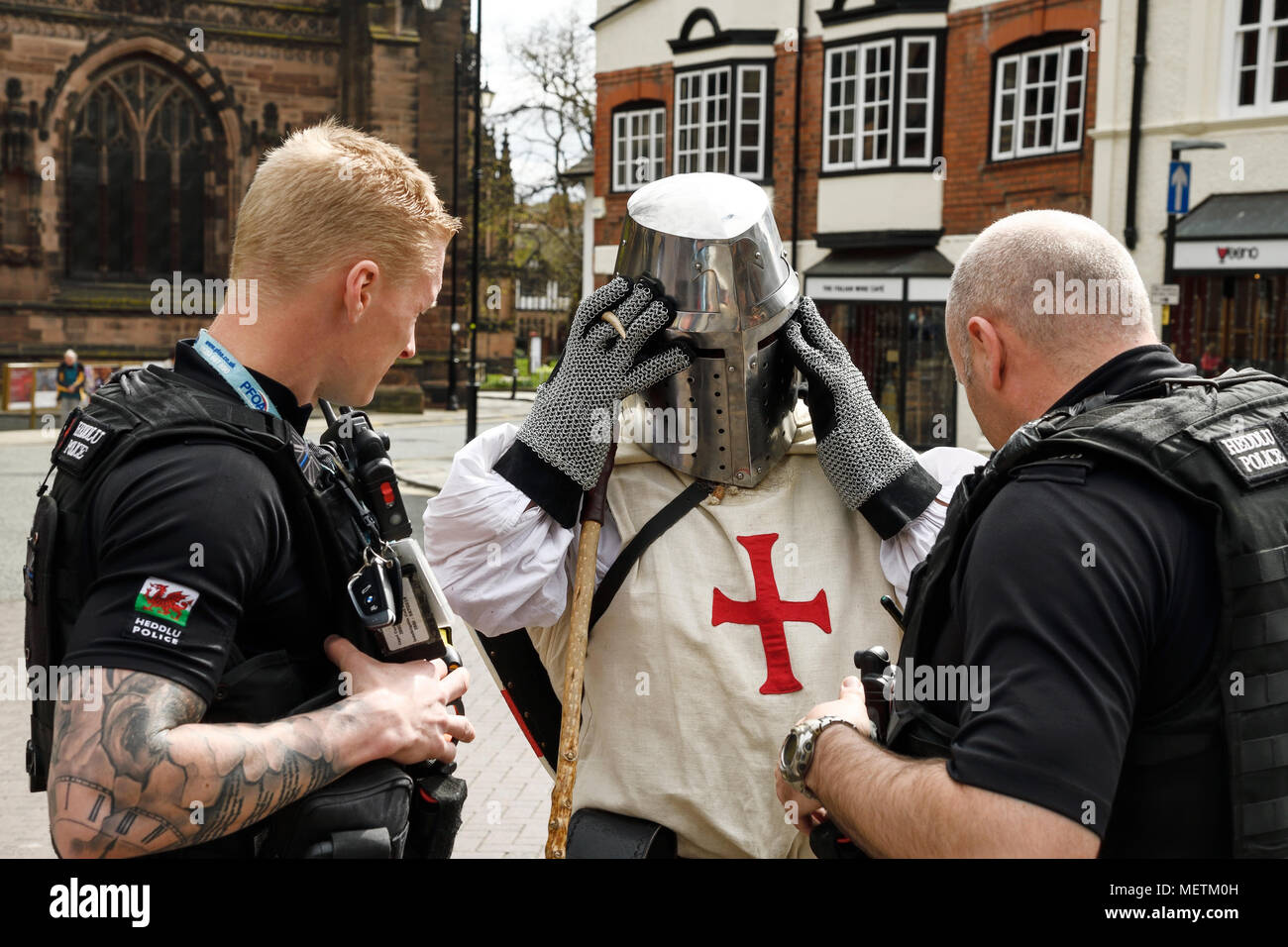 Chester, UK. 23rd April 2018. Local police talk to a performer in the St George's Day parade through the city centre. The parade includes street performance, theatre and music with local school children performing many supporting roles. Credit: Andrew Paterson/Alamy Live News - Stock Image
