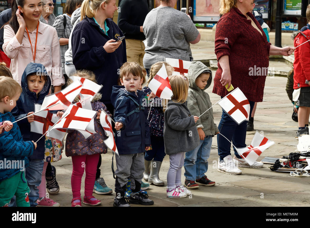 Chester, UK. 23rd April 2018. Children wave flags at the St George's Day parade through the city centre. The parade includes street performance, theatre and music with local school children performing many supporting roles. Credit: Andrew Paterson/Alamy Live News - Stock Image