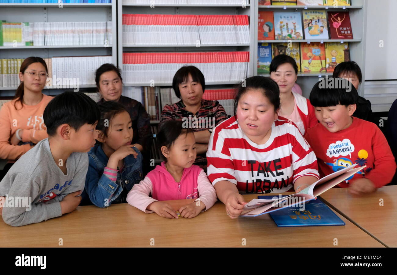 Beijing, China. 23rd Apr, 2018. A librarian reads fairy tales for children during a reading activity at the library of Kangzhuang Township in Yanqing District in Beijing, capital of China, April 23, 2018. April 23 marks the World Book Day, which was promoted by UNESCO as a worldwide celebration of reading since 1995. Credit: Li Xin/Xinhua/Alamy Live News Stock Photo