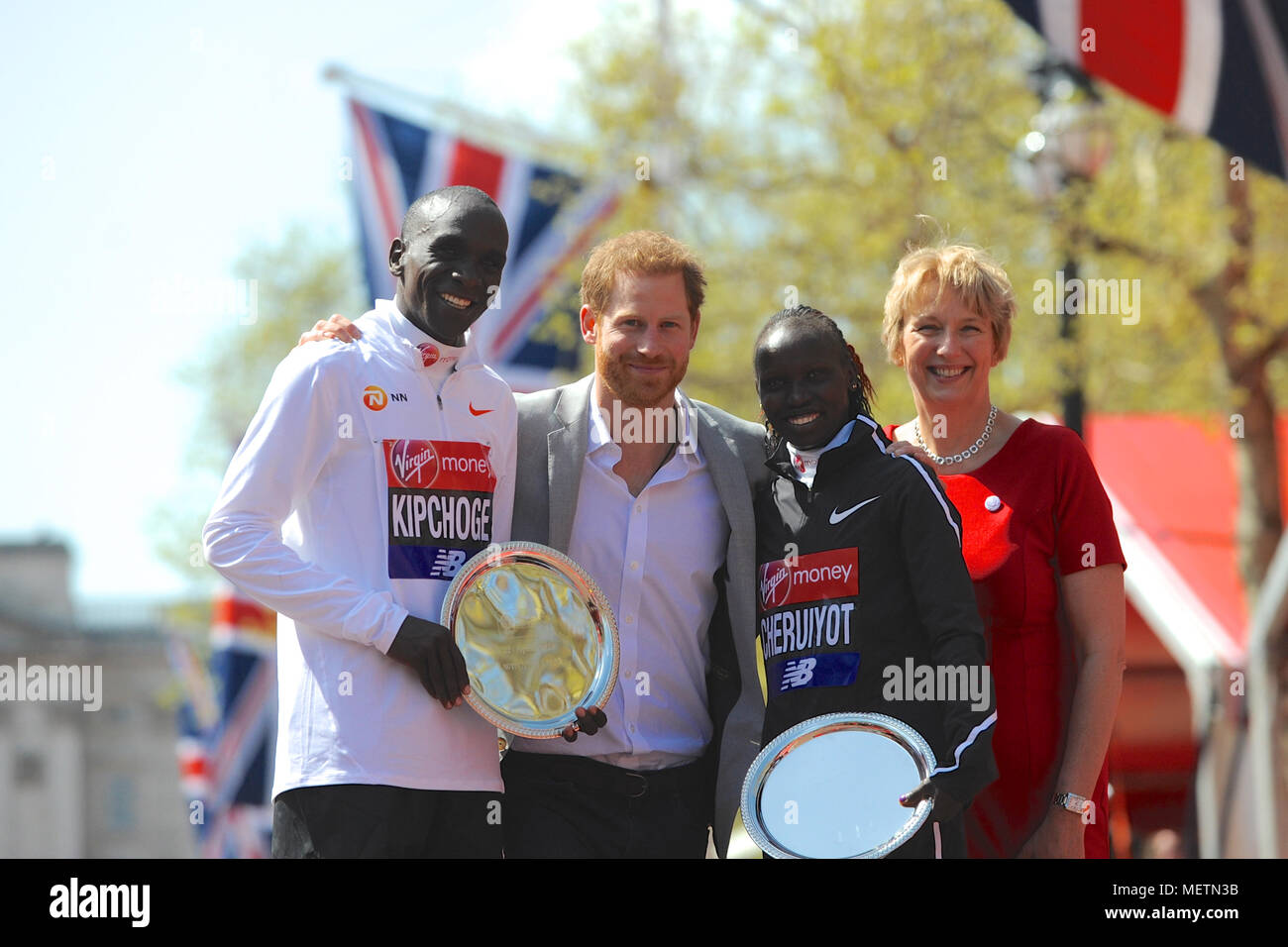 Elud Kipchoge (KEN) and Vivian Cheruiyot (KEN) on the podium with His Royal Highness Prince Harry and  Anne Gadhia (CEO of Virgin Money UK) during the prize giving ceremony for the Virgin Money London Marathon Wheelchair Races, The Mall, London, United Kingdom.  Eliud Kipchoge had earlier confirmed his status as the king of the marathon when he won the Virgin Money London Marathon men's race for the third time with a time of 2:04:17.  Cheruiyot ran a perfectly judged race to take the title in the elite women's race and become the fourth fastest woman of all time over the gruelling marathon dis Stock Photo