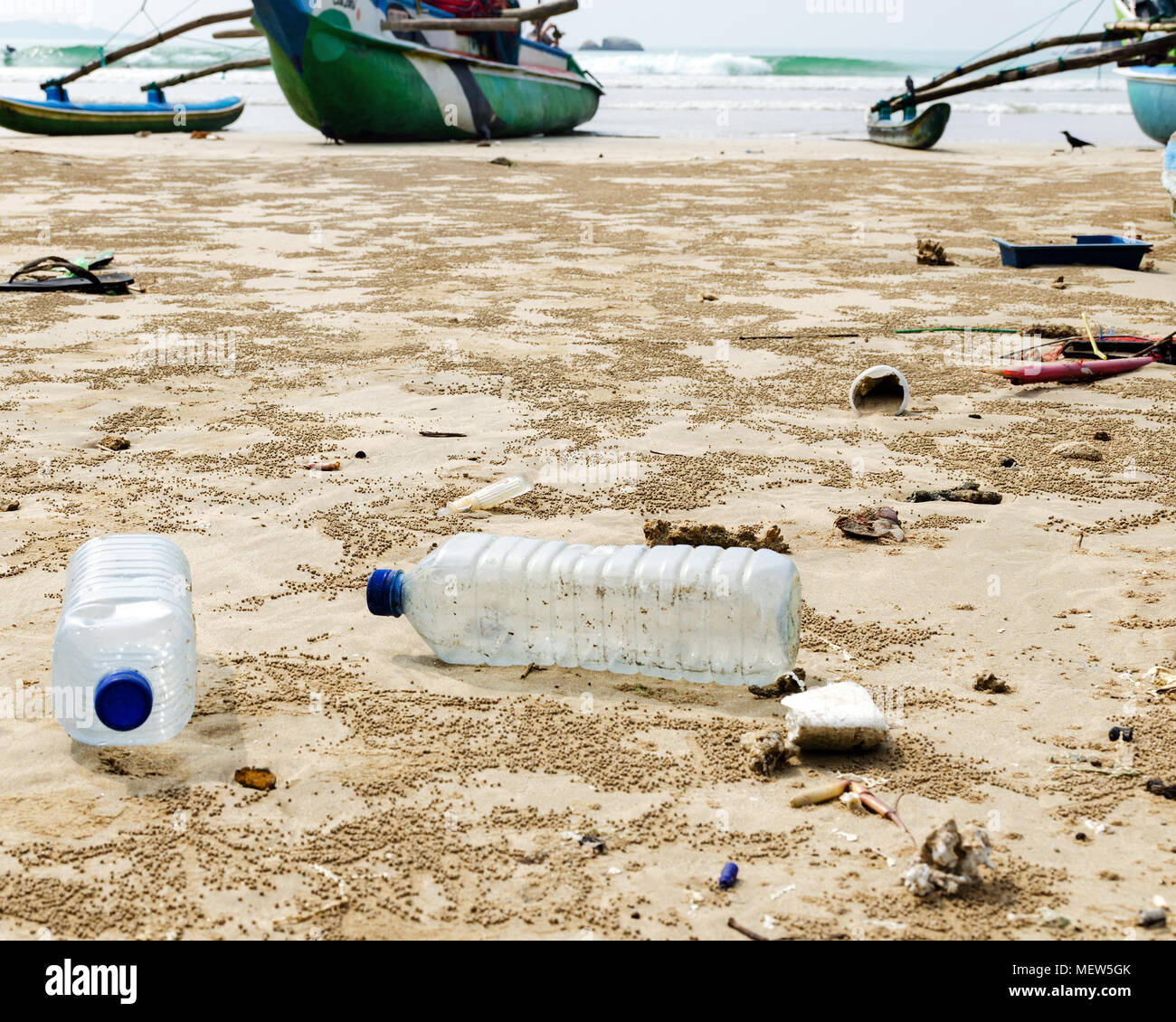 Empty used plastic bottles and other waste thrown out at the sea beach on background is fishing boats, environmental pollution, ecology degradation. - Stock Image