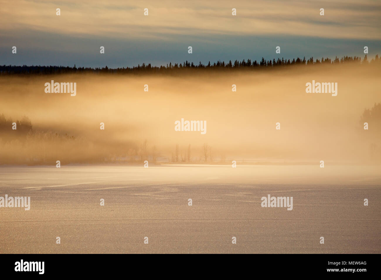 Vapors rising from a frozen lake are illuminated by the setting sun. - Stock Image