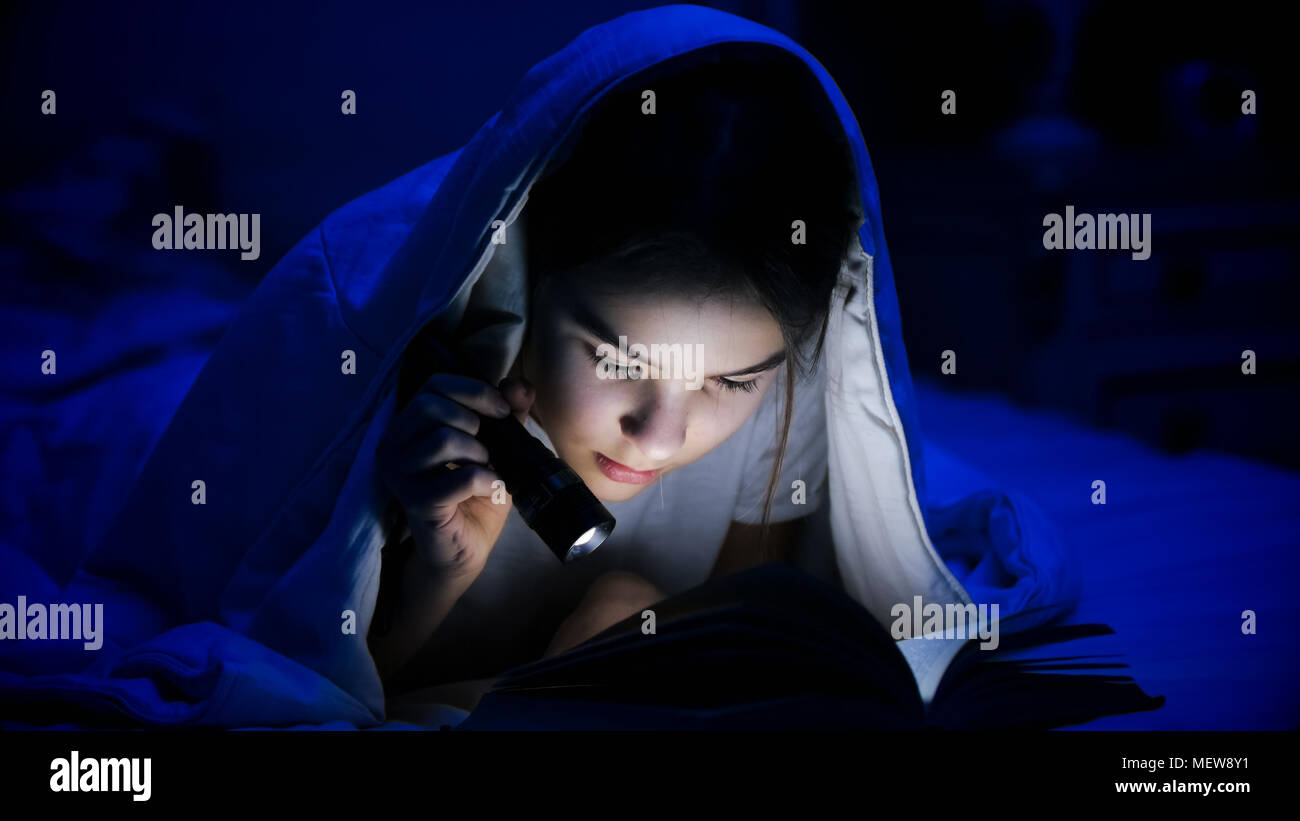 Girl reading scary book stock photos girl reading scary book stock portrait of beautiful girl with flashlight reading book in bed stock image sciox Gallery