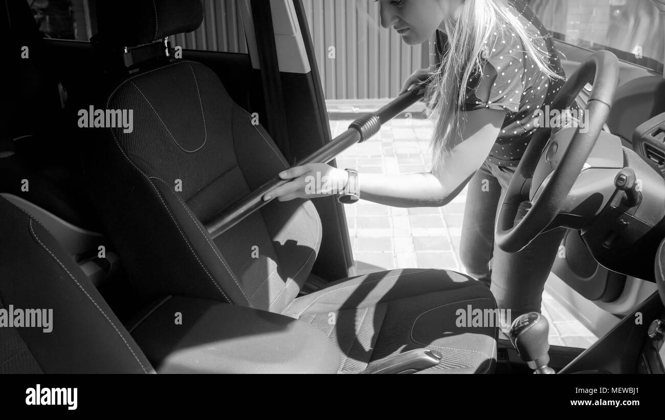 Black And White Photo Of Young Woman Cleaning Car Seat With Vacuum