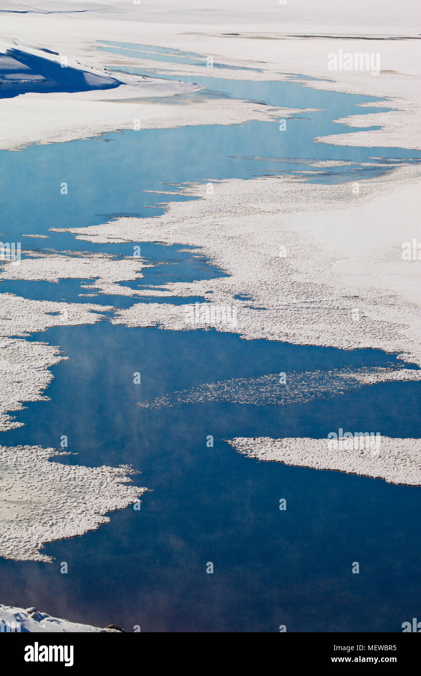 Thin ice is covering a lake. Wisps of haze are rising from the places with open water. - Stock Image