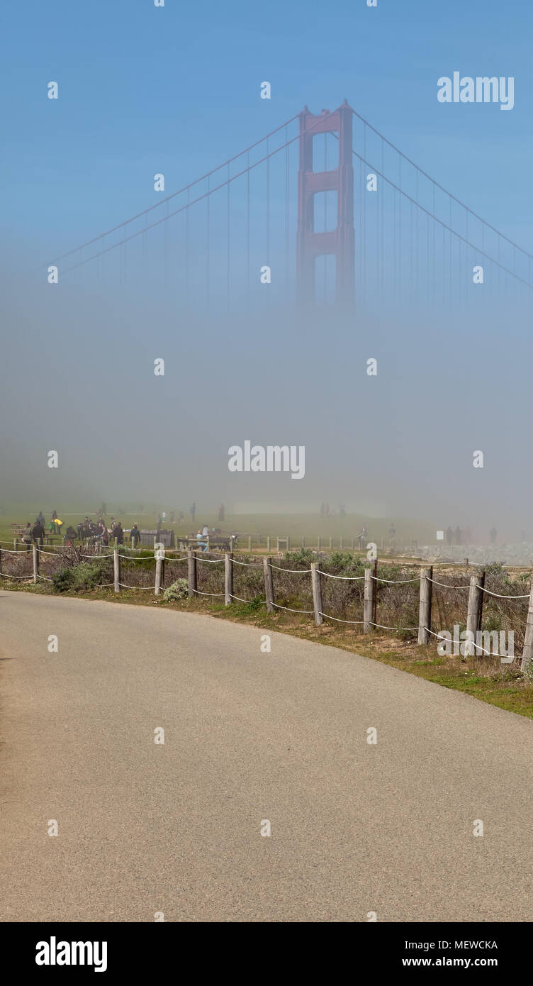 View of the Golden Gate Bridge, slowly visible as the fog started to clear up, from Crissy Field in San Francisco, California, United States. - Stock Image
