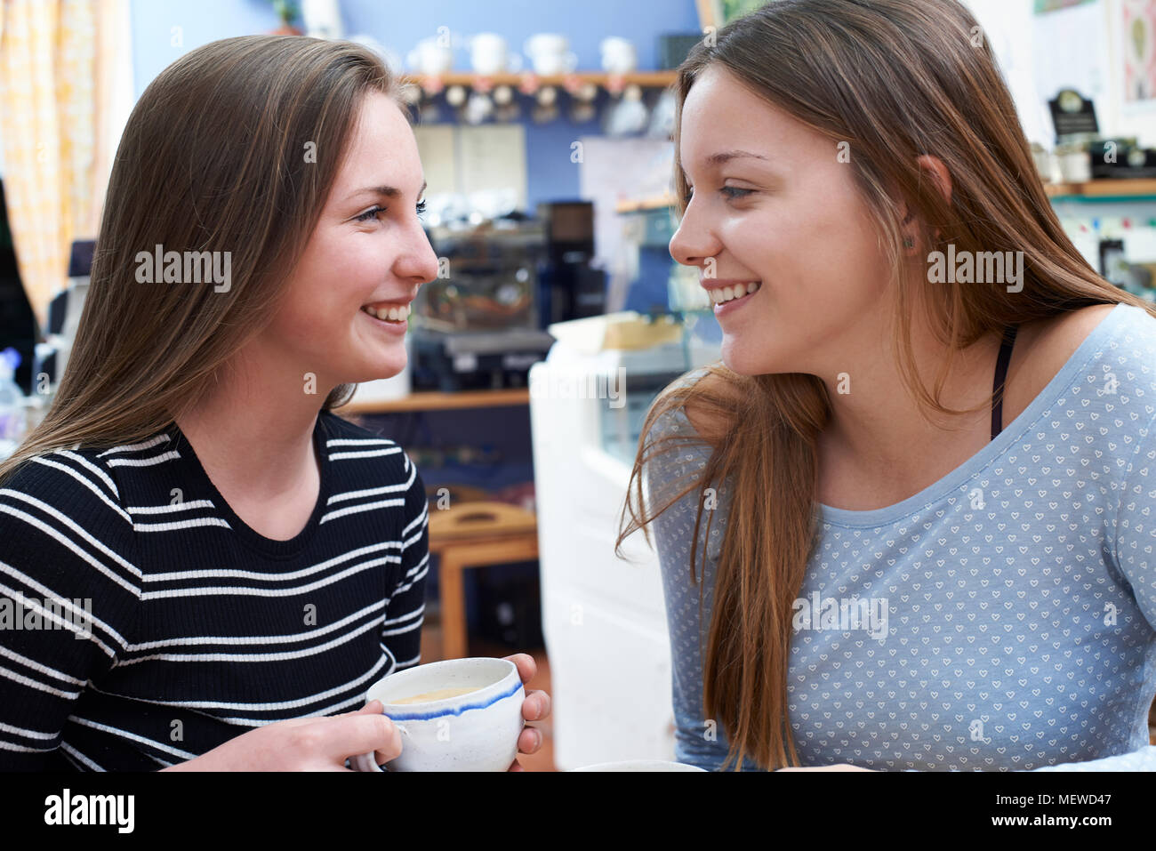 Two Female Teenage Friends Meeting In Cafe - Stock Image