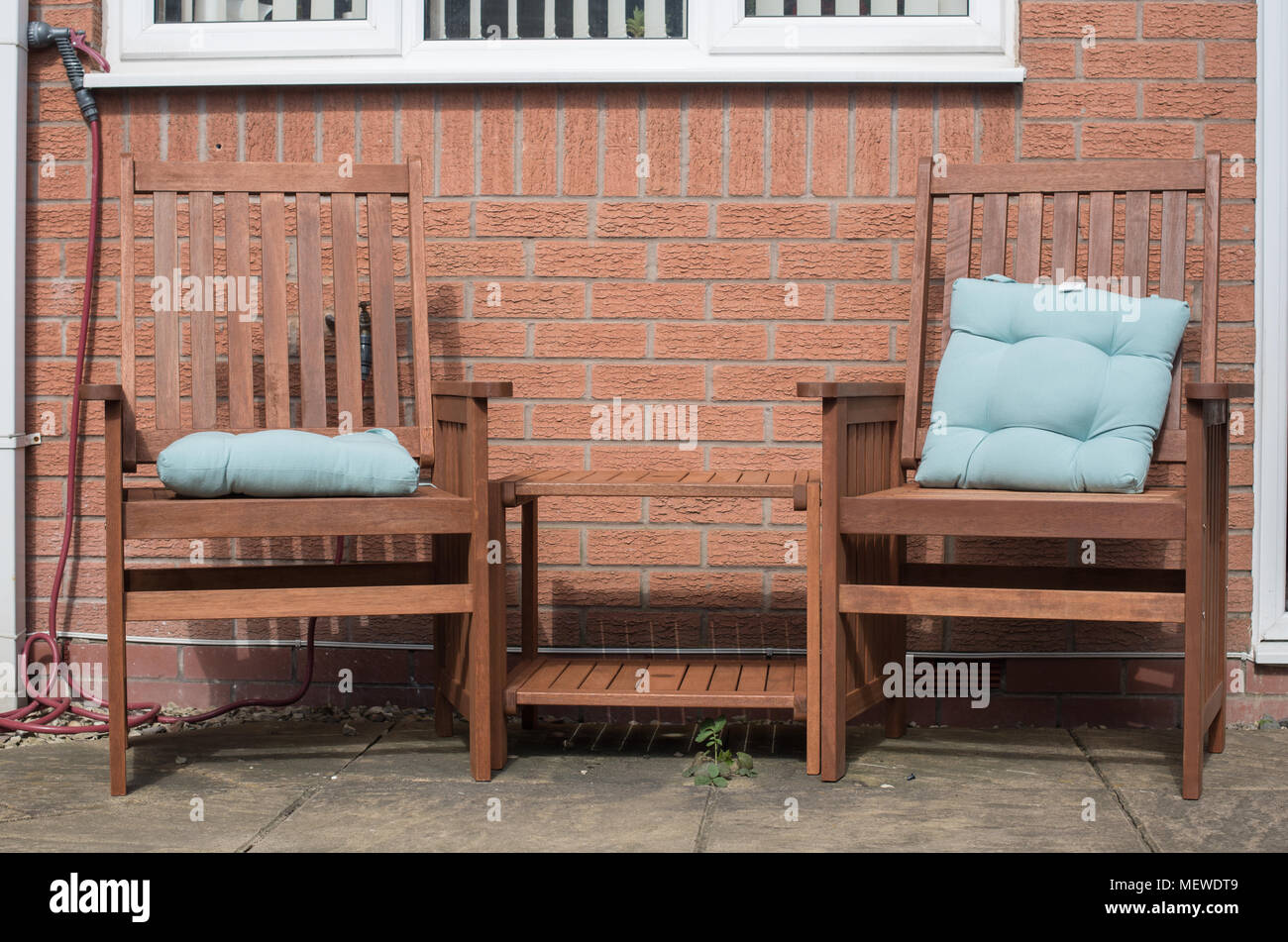Relaxing garden chairs with blue cushions on a patio in bright sunshine - Stock Image
