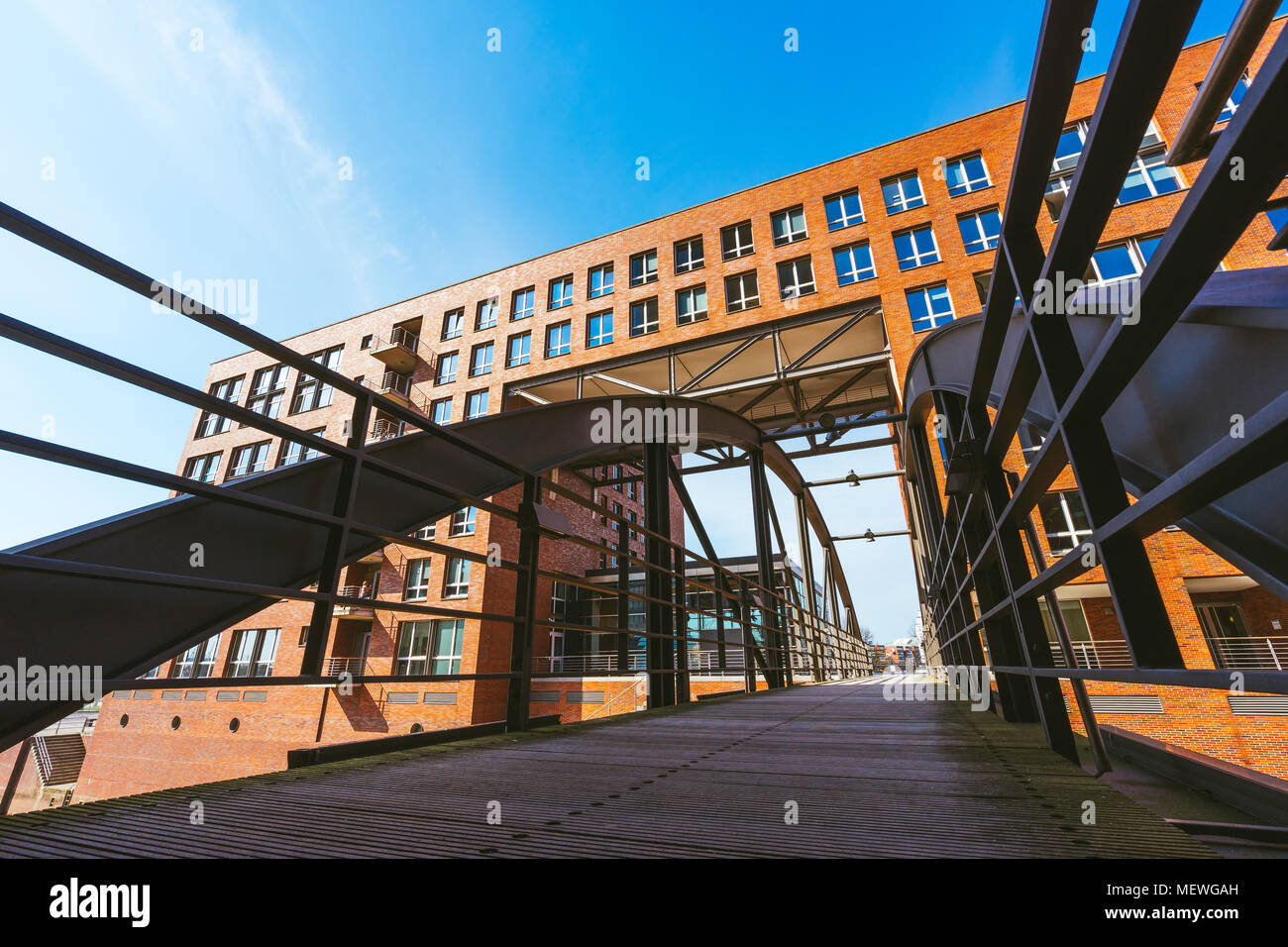 Famous landmark old Speicherstadt in Hamburg, build with red bricks. Bridge in low angle view. - Stock Image