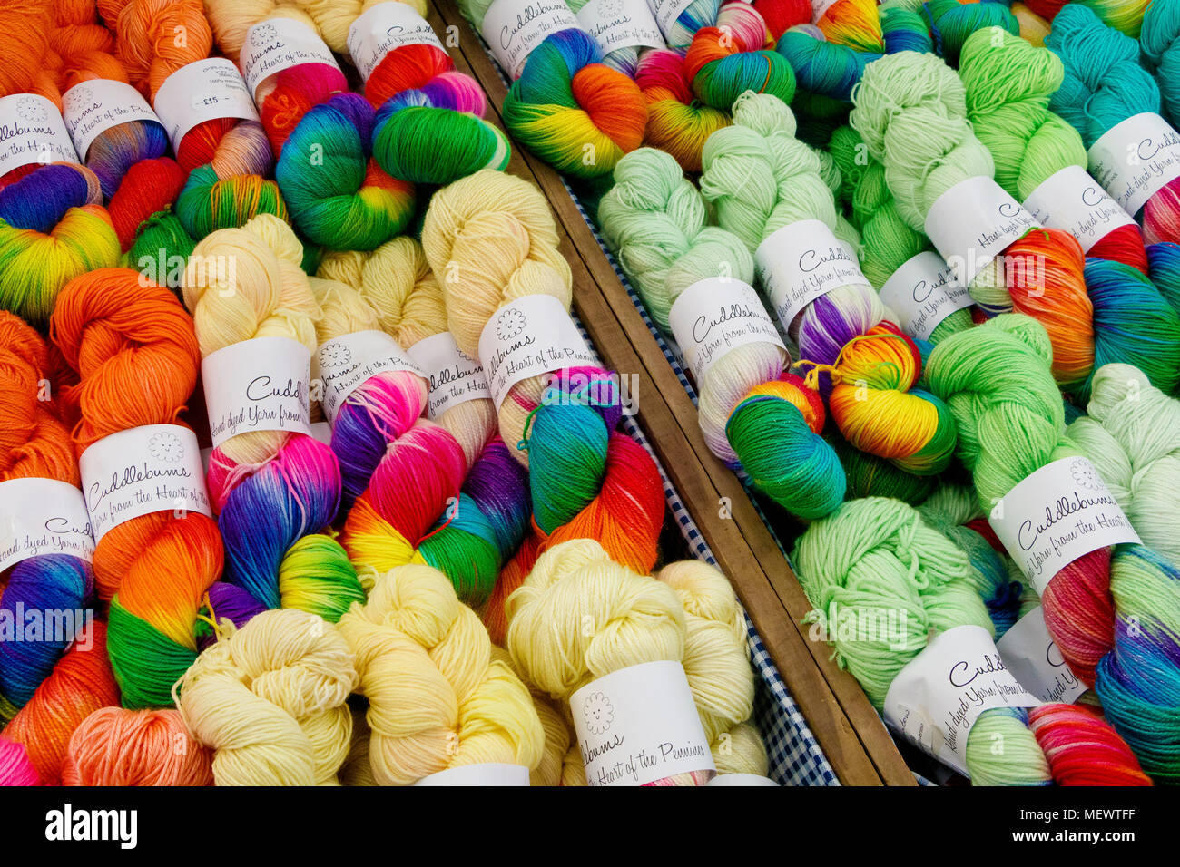Multi-coloured skeins of wool on a retailers stall at Yarndale, Skipton, North Yorkshire, UK. - Stock Image