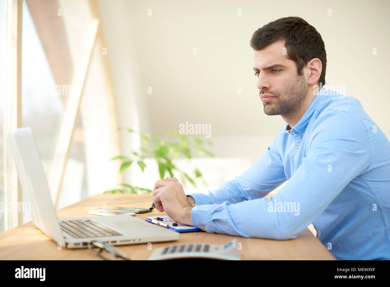 Portrait of young businessman sitting at office desk in front of laptop and looking thoughtfull while working online. Home office. - Stock Image