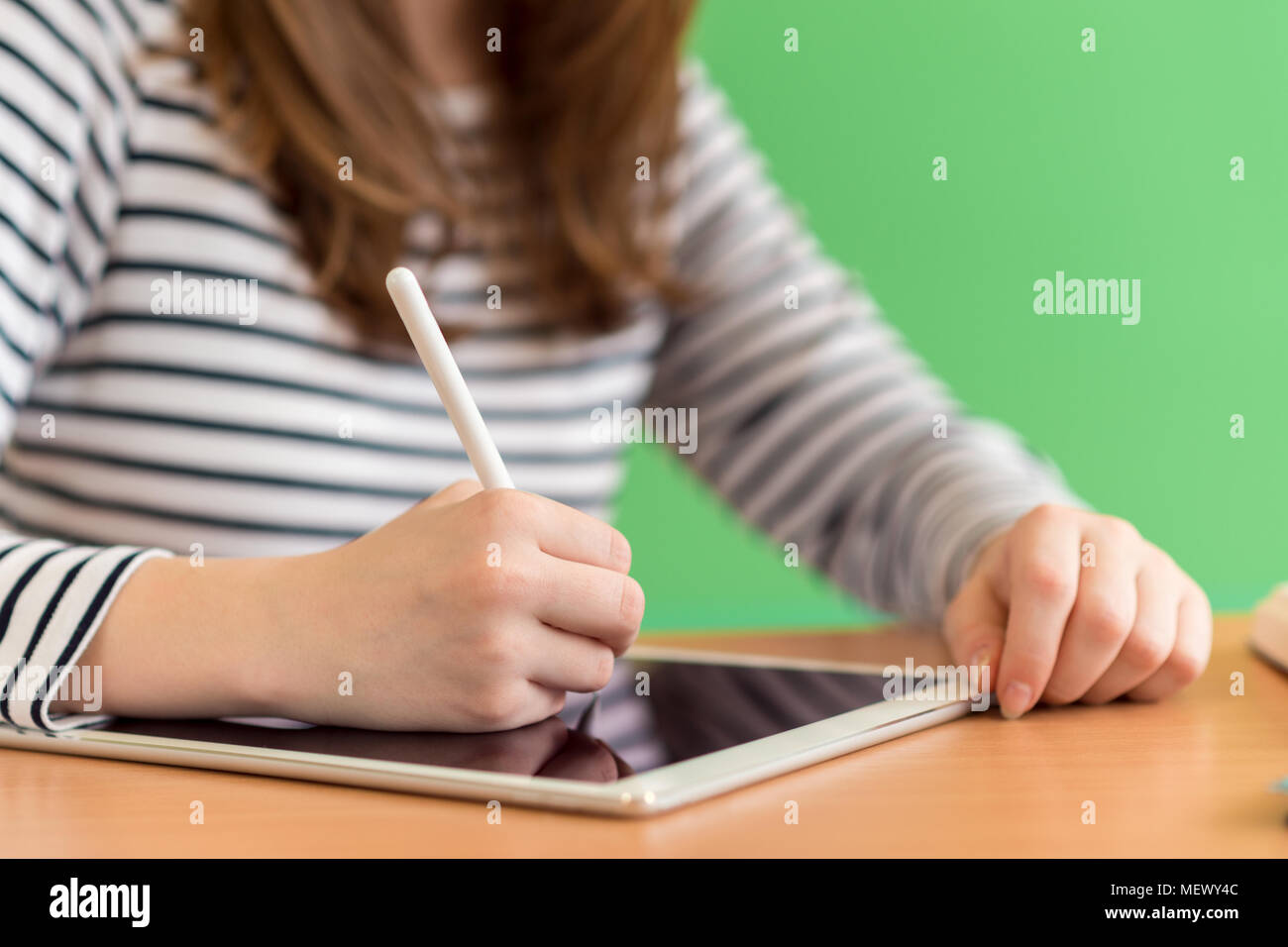 Young female student writing notes using digital tablet during class. Generation Z Education concept. - Stock Image